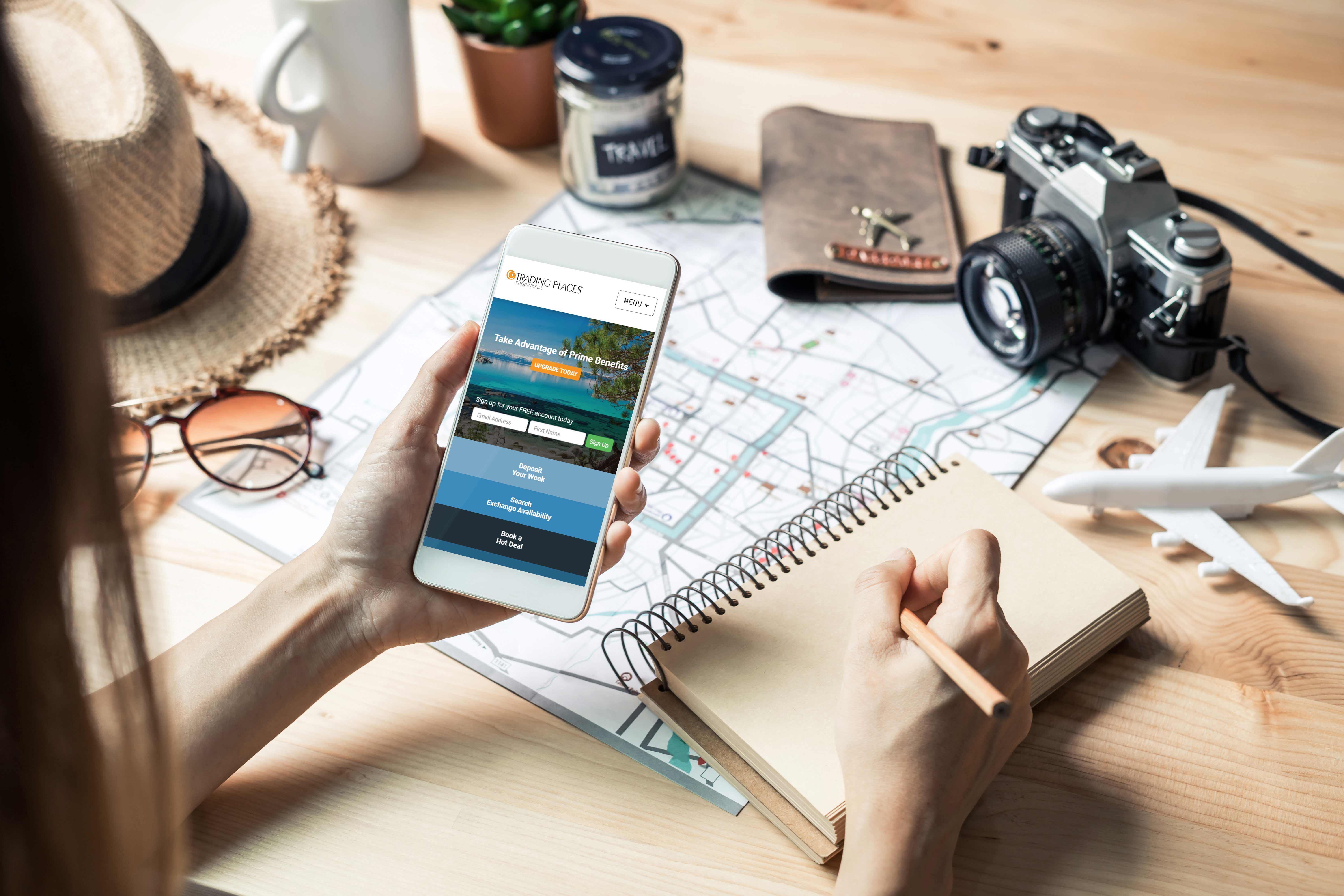 Traveler with map, pen and pad searches for timeshare exchange help on Trading Places mobile site